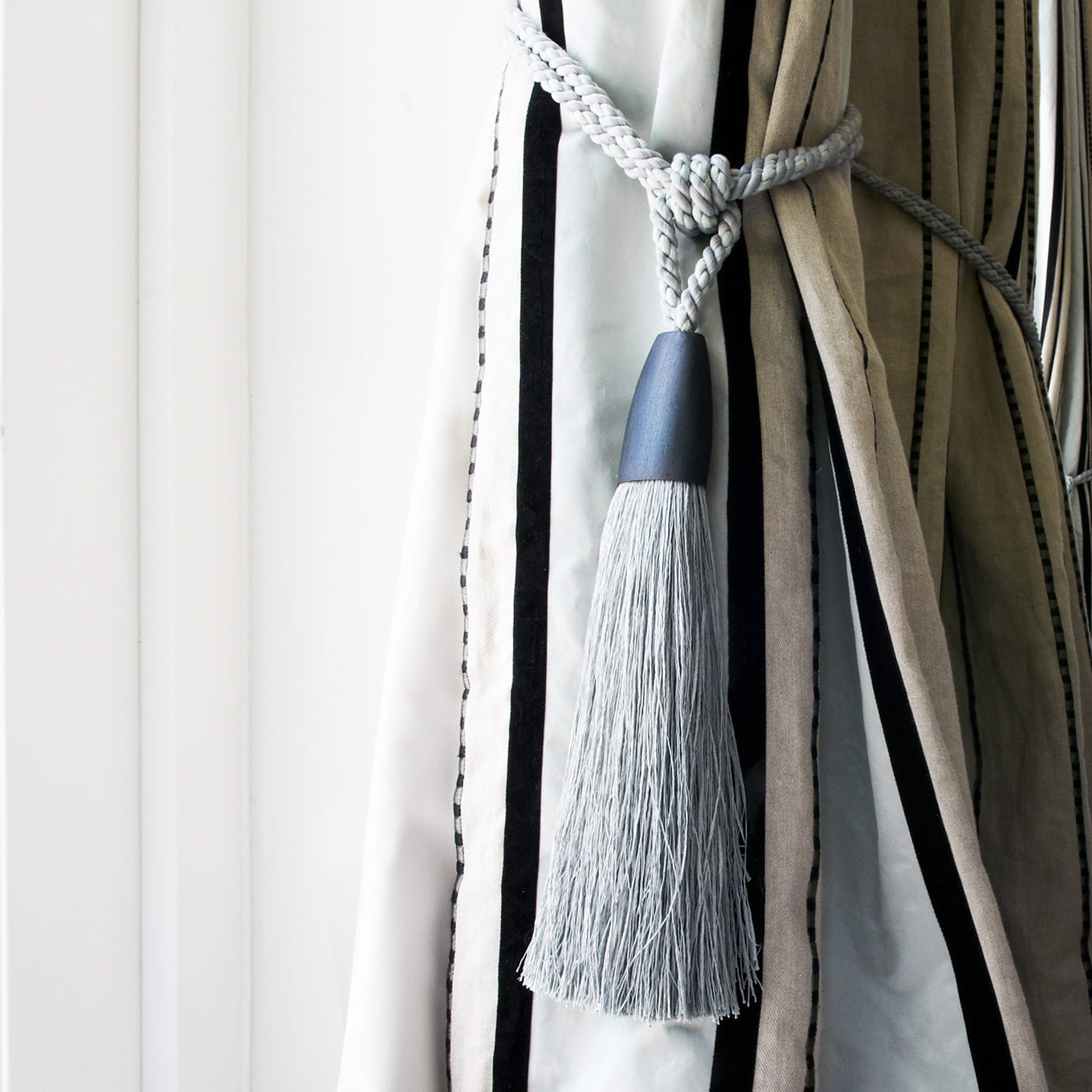 Striped curtains made by Thomas Coombes Interior Design with tie backs.